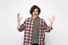 Πορτρέτο του τρελλού κραυγάζοντας νεαρού άνδρα στα περιστασιακά ενδύματα που φαίνεται χέρια διάδοσης καμερών απομονωμένος στο άσπ στοκ φωτογραφία