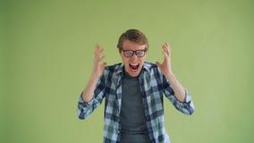 Πορτρέτο του τρελλού υ όμορφου τύπου προσώπων στα γυαλιά που φωνάζουν στο πράσινο υπόβαθρο απόθεμα βίντεο