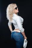 Πορτρέτο του τρόπου ζωής της μοντέρνης νέας γυναίκας με τα σγουρά ξανθά μαλλιά, γυαλιά ηλίου, άσπρο σακάκι δέρματος, τζιν παντελό Στοκ Φωτογραφίες