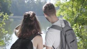 Πορτρέτο του τύπου και του νέου χαριτωμένου κοριτσιού που στέκονται στο riverbank στο δάσος με τα σακίδια πλάτης που δείχνουν μακ φιλμ μικρού μήκους