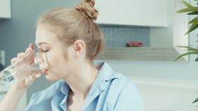 Πορτρέτο του υγιούς νέου ξανθού πόσιμου νερού γυναικών στο σπίτι απόθεμα βίντεο