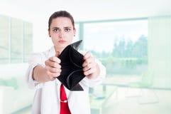 Πορτρέτο του λυπημένου γιατρού που παρουσιάζει κενό πορτοφόλι δέρματος Στοκ φωτογραφία με δικαίωμα ελεύθερης χρήσης
