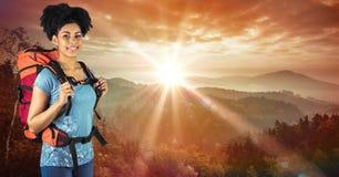 Πορτρέτο του φέρνοντας σακιδίου πλάτης hipster στεμένος στον απότομο βράχο ενάντια στον ουρανό Στοκ Φωτογραφίες
