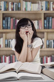 Πορτρέτο του φοβησμένου σπουδαστή στη βιβλιοθήκη Στοκ φωτογραφία με δικαίωμα ελεύθερης χρήσης