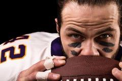 Πορτρέτο του φορέα αμερικανικού ποδοσφαίρου που κρατά μια σφαίρα και που εξετάζει τη κάμερα στοκ φωτογραφίες