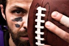 Πορτρέτο του φορέα αμερικανικού ποδοσφαίρου που κρατά μια σφαίρα και που εξετάζει τη κάμερα στοκ φωτογραφία με δικαίωμα ελεύθερης χρήσης