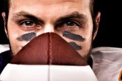 Πορτρέτο του φορέα αμερικανικού ποδοσφαίρου που κρατά μια σφαίρα και που εξετάζει τη κάμερα στοκ εικόνες με δικαίωμα ελεύθερης χρήσης