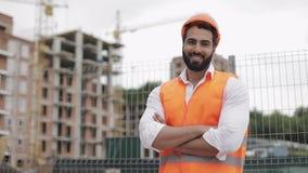 Πορτρέτο του χαμογελώντας ατόμου αρχιτεκτόνων που στέκεται στο εργοτάξιο οικοδομής με τα διασχισμένα χέρια που εξετάζουν τη κάμερ απόθεμα βίντεο