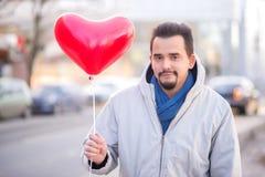 Πορτρέτο του χαμογελώντας ατόμου με ένα καρδιά-διαμορφωμένο κόκκινο μπαλόνι που στέκεται σε μια οδό Έννοια ημέρας βαλεντίνων στοκ εικόνα με δικαίωμα ελεύθερης χρήσης