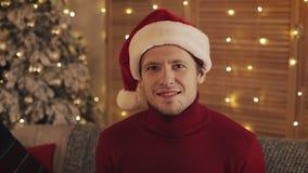 Πορτρέτο του χαμογελώντας ελκυστικού ατόμου στο καπέλο santa που εξετάζει τη κάμερα στο υπόβαθρο χριστουγεννιάτικων δέντρων κίνησ απόθεμα βίντεο