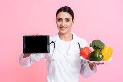 Πορτρέτο του χαμογελώντας θηλυκού γιατρού με το πιάτο εκμετάλλευσης στηθοσκοπίων των λαχανικών και της ταμπλέτας που απομονώνοντα στοκ φωτογραφία με δικαίωμα ελεύθερης χρήσης