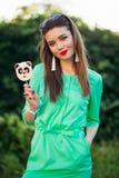 Πορτρέτο του χαμογελώντας κοριτσιού στο πράσινο φόρεμα με την καραμέλα στο ραβδί υπό εξέταση Στοκ Εικόνα
