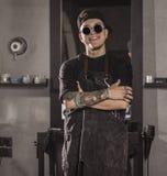 Πορτρέτο του χαμογελώντας κουρέα στα γυαλιά που στέκονται στο σαλόνι του και που εξετάζουν τη κάμερα Στοκ Εικόνες