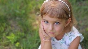 Πορτρέτο του χαμογελώντας μικρού κοριτσιού στο πάρκο στο πράσινο υπόβαθρο χλόης Heterochromia φιλμ μικρού μήκους