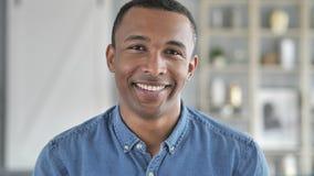Πορτρέτο του χαμογελώντας νέου αφρικανικού ατόμου που εξετάζει τη κάμερα στοκ εικόνα με δικαίωμα ελεύθερης χρήσης