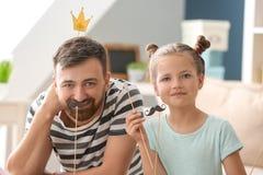 Πορτρέτο του χαμογελώντας πατέρα και της κόρης με το τεχνητές mustache και την κορώνα στο σπίτι στοκ φωτογραφία με δικαίωμα ελεύθερης χρήσης