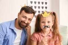 Πορτρέτο του χαμογελώντας πατέρα και της κόρης με το τεχνητές mustache και την κορώνα στο σπίτι στοκ εικόνες με δικαίωμα ελεύθερης χρήσης