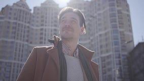 Πορτρέτο του χαμογελώντας όμορφου βέβαιου ατόμου στο καφετί παλτό που στέκεται στην οδό πόλεων που κοιτάζει γύρω Υψηλά κτήρια μέσ φιλμ μικρού μήκους