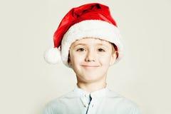 Πορτρέτο του χαμογελώντας αγοριού παιδιών στο κόκκινο καπέλο Santa Στοκ Εικόνα