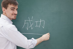 Πορτρέτο του χαμογελώντας αρσενικού δασκάλου μπροστά από τον πίνακα κιμωλίας που γράφει, κινεζικοί χαρακτήρες Στοκ εικόνα με δικαίωμα ελεύθερης χρήσης