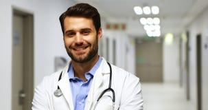 Πορτρέτο του χαμογελώντας αρσενικού γιατρού στο διάδρομο φιλμ μικρού μήκους