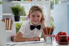 Πορτρέτο του χαμογελώντας επιχειρηματία με τα έγγραφα στο γραφείο Στοκ εικόνες με δικαίωμα ελεύθερης χρήσης