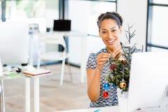 Πορτρέτο του χαμογελώντας εργαζομένου γραφείων θηλυκών με το χριστουγεννιάτικο δέντρο Στοκ Φωτογραφίες