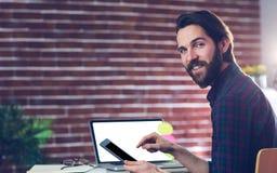Πορτρέτο του χαμογελώντας δημιουργικού επιχειρηματία που χρησιμοποιεί την ψηφιακή ταμπλέτα Στοκ φωτογραφίες με δικαίωμα ελεύθερης χρήσης