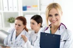 Πορτρέτο του χαμογελώντας θηλυκού γιατρού ιατρικής που κρατά το μπλε έγγραφο Στοκ Εικόνες