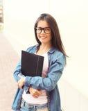 Πορτρέτο του χαμογελώντας κοριτσιού σπουδαστών στα γυαλιά με το φάκελλο στοκ φωτογραφία με δικαίωμα ελεύθερης χρήσης