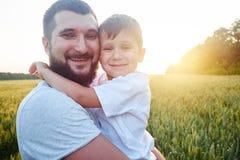 Πορτρέτο του χαμογελώντας μπαμπά και του γιου κατά τη διάρκεια του ηλιοβασιλέματος στον τομέα Στοκ Εικόνες