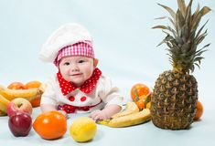 Πορτρέτο του χαμογελώντας μωρού που φορά ένα καπέλο αρχιμαγείρων που περιβάλλεται από τα φρούτα Στοκ Εικόνες