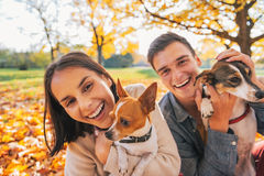 Πορτρέτο του χαμογελώντας νέου ζεύγους με τα σκυλιά υπαίθρια στοκ φωτογραφία με δικαίωμα ελεύθερης χρήσης
