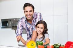 Πορτρέτο του χαμογελώντας πατέρα και της κόρης που χρησιμοποιούν το lap-top στοκ φωτογραφία με δικαίωμα ελεύθερης χρήσης