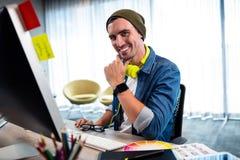 Πορτρέτο του χαμογελώντας περιστασιακού ατόμου που εργάζεται στο γραφείο υπολογιστών Στοκ φωτογραφίες με δικαίωμα ελεύθερης χρήσης