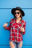 Πορτρέτο του χαμογελώντας hipster κοριτσιού μόδας ομορφιάς στο καπέλο και των γυαλιών ηλίου στο μπλε υπόβαθρο Στοκ Φωτογραφίες