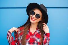 Πορτρέτο του χαμογελώντας hipster κοριτσιού μόδας ομορφιάς στο καπέλο και των γυαλιών ηλίου στο μπλε υπόβαθρο Στοκ εικόνες με δικαίωμα ελεύθερης χρήσης