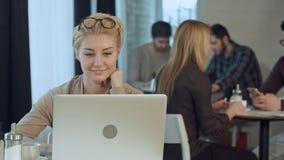 Πορτρέτο του χαμόγελου της αρκετά νέας επιχειρησιακής γυναίκας που αναβάλλει τα γυαλιά που κάθονται στο lap-top καφέδων woth απόθεμα βίντεο