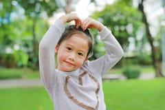Πορτρέτο του χαμόγελου χαριτωμένο λίγου ασιατικού κοριτσιού παιδιών στον πράσινο κήπο με την παραγωγή των χεριών της για την καρδ στοκ φωτογραφίες με δικαίωμα ελεύθερης χρήσης