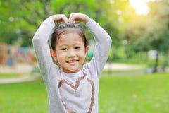 Πορτρέτο του χαμόγελου χαριτωμένο λίγου ασιατικού κοριτσιού παιδιών στον πράσινο κήπο με την παραγωγή των χεριών της για την καρδ στοκ φωτογραφίες