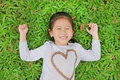 Πορτρέτο του χαμόγελου χαριτωμένο λίγου ασιατικού κοριτσιού παιδιών που βρίσκεται στον πράσινο χορτοτάπητα στοκ φωτογραφία