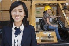 Πορτρέτο του χαμόγελου γυναικών ενώ θηλυκό οδηγώντας forklift βιομηχανικών εργατών φορτηγό στο υπόβαθρο στοκ φωτογραφίες με δικαίωμα ελεύθερης χρήσης
