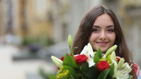 Πορτρέτο του χαμόγελου των νέων μυρίζοντας λουλουδιών γυναικών απόθεμα βίντεο