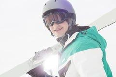 Πορτρέτο του χαμόγελου των φέρνοντας σκι νεαρών άνδρων ενάντια στο σαφή ουρανό στοκ εικόνες με δικαίωμα ελεύθερης χρήσης