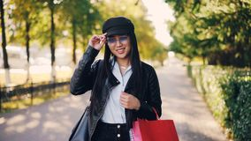 Πορτρέτο του χαριτωμένου ασιατικού κοριτσιού στο σακάκι δέρματος και της ΚΑΠ που εξετάζει τη κάμερα, που χαμογελά και που κρατά τ απόθεμα βίντεο