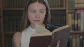 Πορτρέτο του χαριτωμένου κοριτσιού με μια δερματοστιξία στο βιβλίο ανάγνωσης ώμων στενό στον επάνω βιβλιοθηκών Ελκυστικό νέο κορί απόθεμα βίντεο