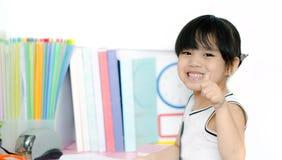 Πορτρέτο του χαριτωμένου κοριτσιού που εξετάζει τη κάμερα και που παρουσιάζει αντίχειρα στοκ εικόνα