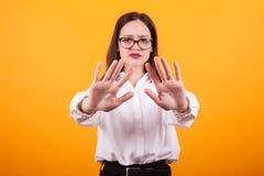 Πορτρέτο του χαριτωμένου κοριτσιού που παρουσιάζει χέρια στη κάμερα στο στούντιο πέρα από το κίτρινο υπόβαθρο στοκ φωτογραφία με δικαίωμα ελεύθερης χρήσης