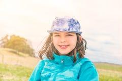Πορτρέτο του χαριτωμένου κοριτσιού στη μπλε ζακέτα και την ΚΑΠ Στοκ Φωτογραφία