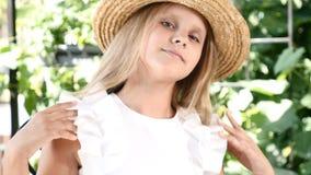 Πορτρέτο του χαριτωμένου κοριτσιού στο καπέλο αχύρου που χαμογελά, σχετικά με την τρίχα και το καπέλο της κλείστε επάνω lifestyle απόθεμα βίντεο